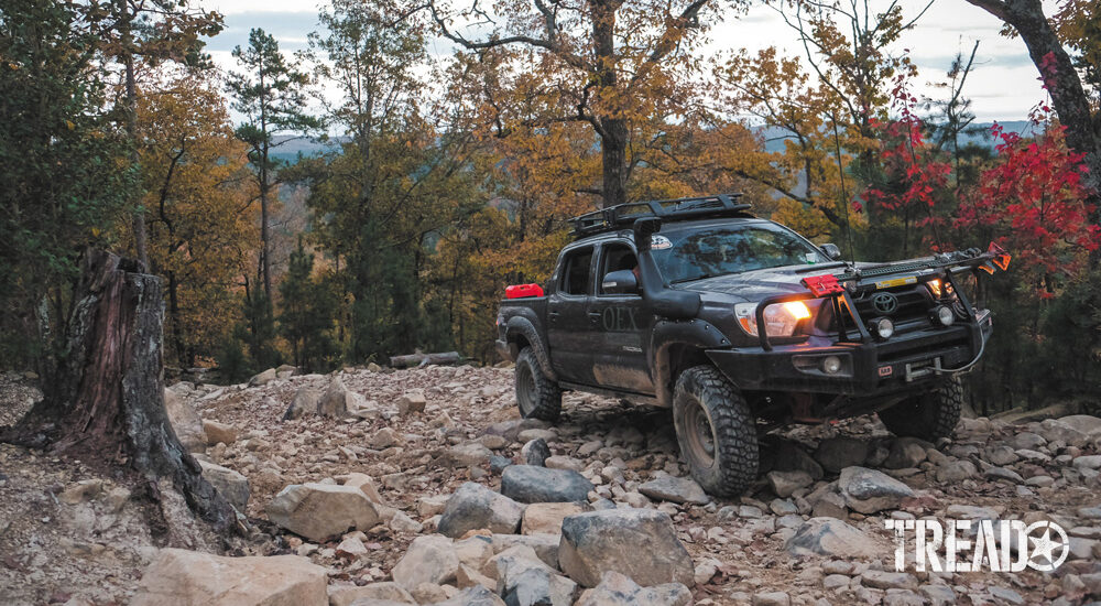 Dark blue Toyota Tacoma drives off road up rocky terrain during Overland Challenge 2020 in Uwharrie National Forest.