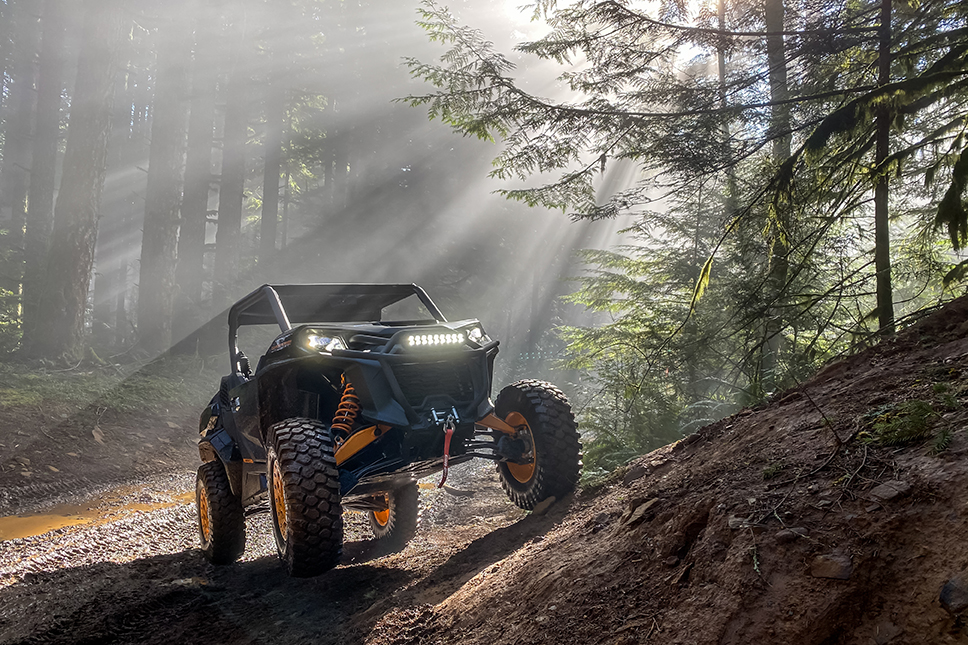 Can-Am Commander XTP Adventure parked on dirt with sun beaming down on it.